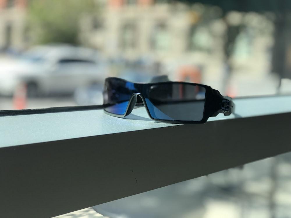 black framed blue lens sunglasses near window