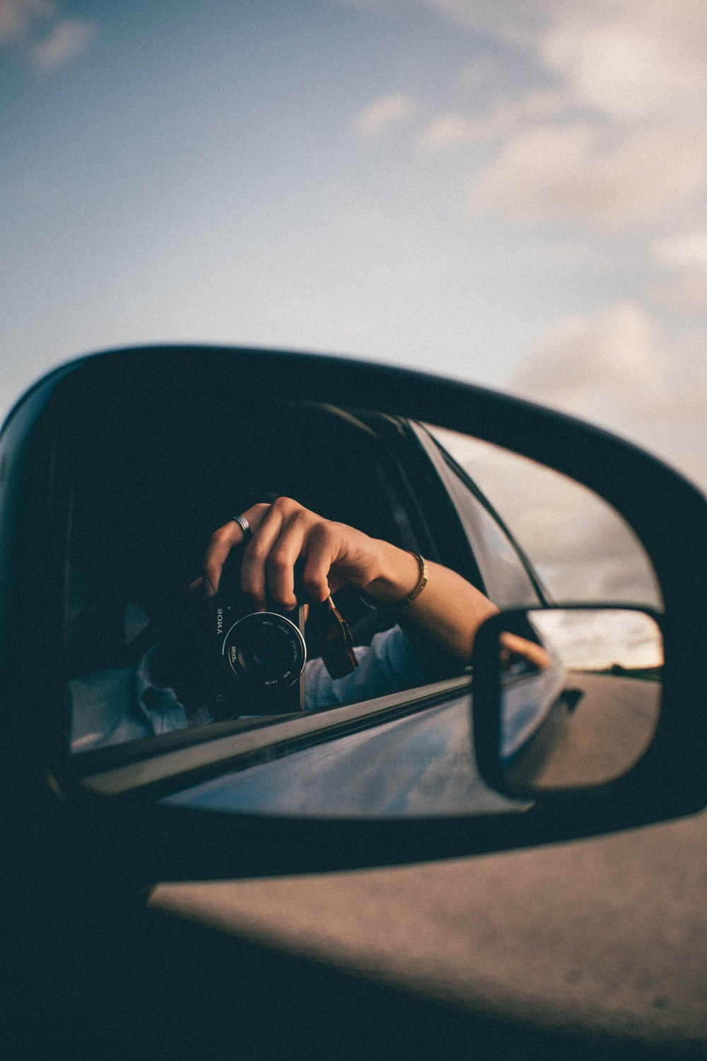 person using camera at the side mirror