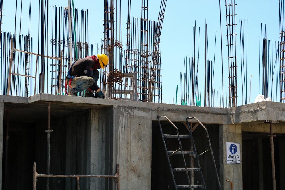 man kneeling on unfinished building during daytime