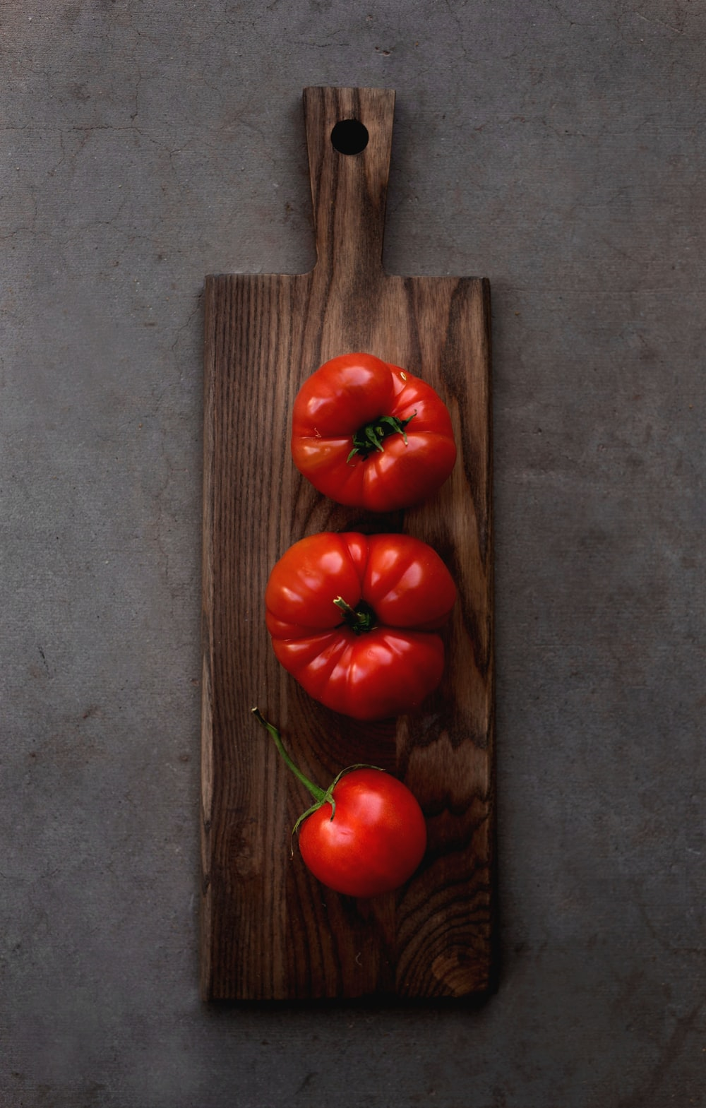 three red tomatoes on chopping board