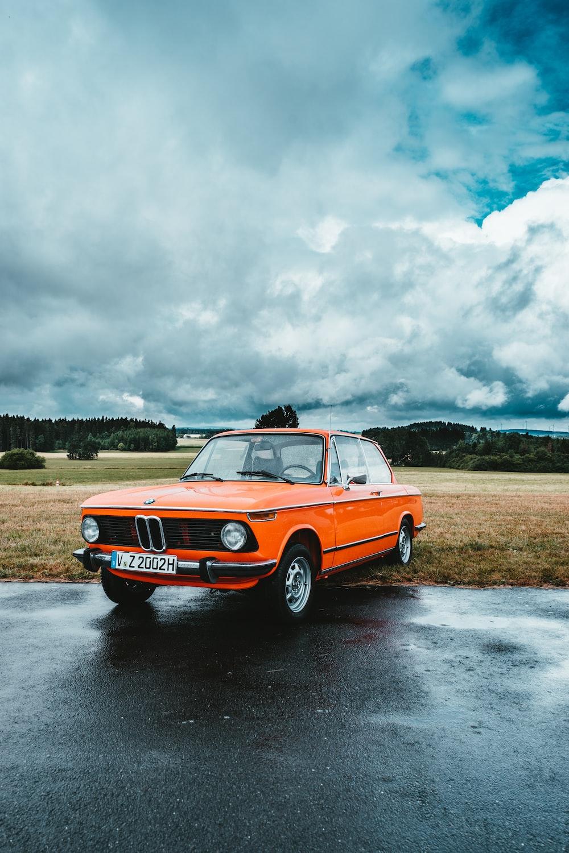 orange BMW sedan parked near grass field