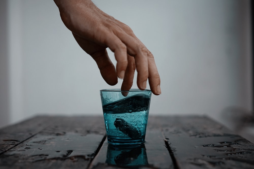 person touching teal drinking glass