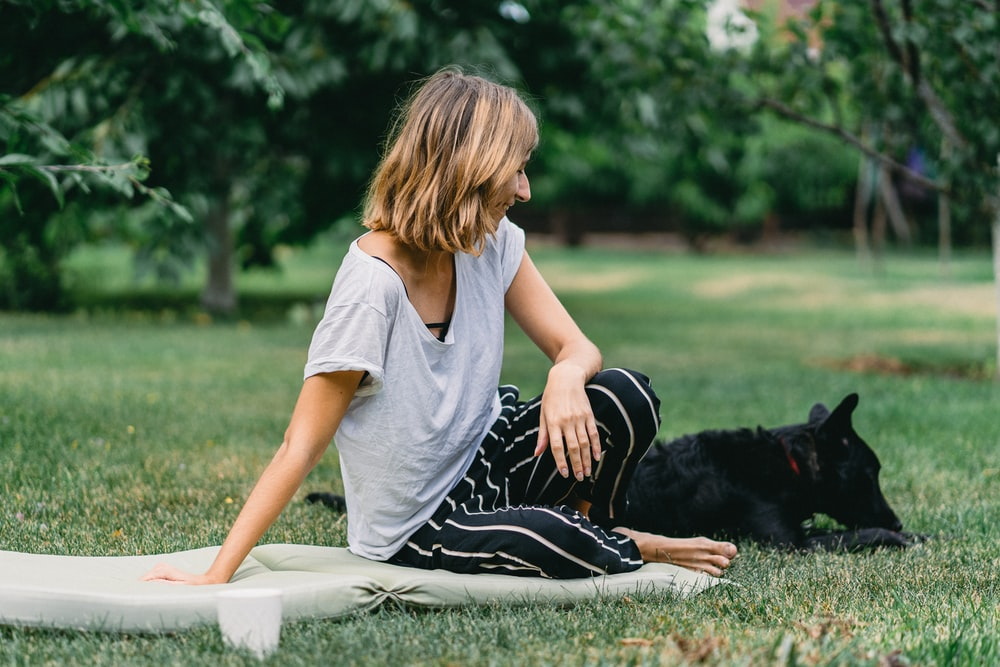 woman sitting on ground beside black dog