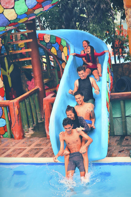 people on blue swimming pool slide
