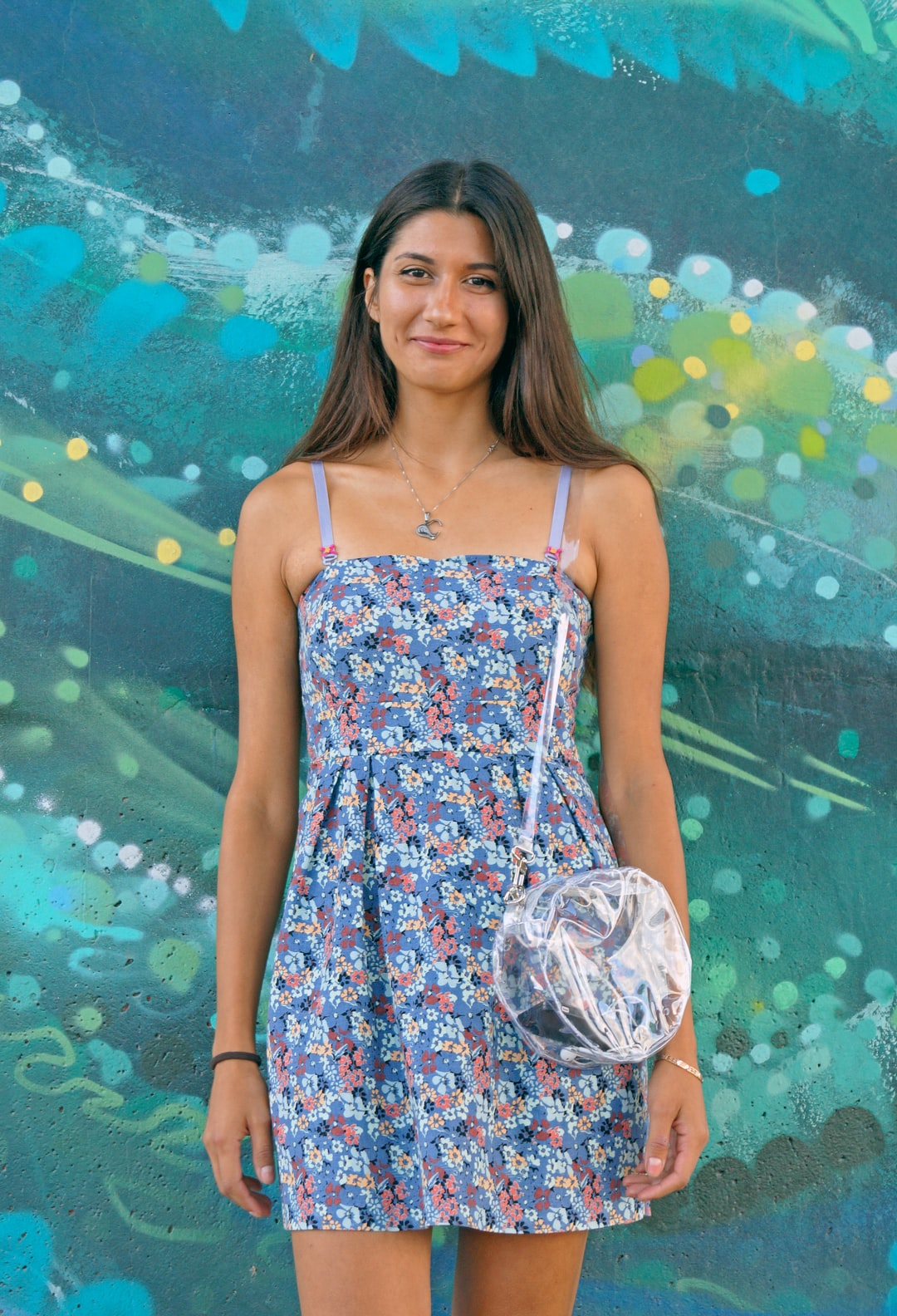 Smiling brunette girl in blue summer floral dress standing in front of turquoise graffiti with transparent clear bag