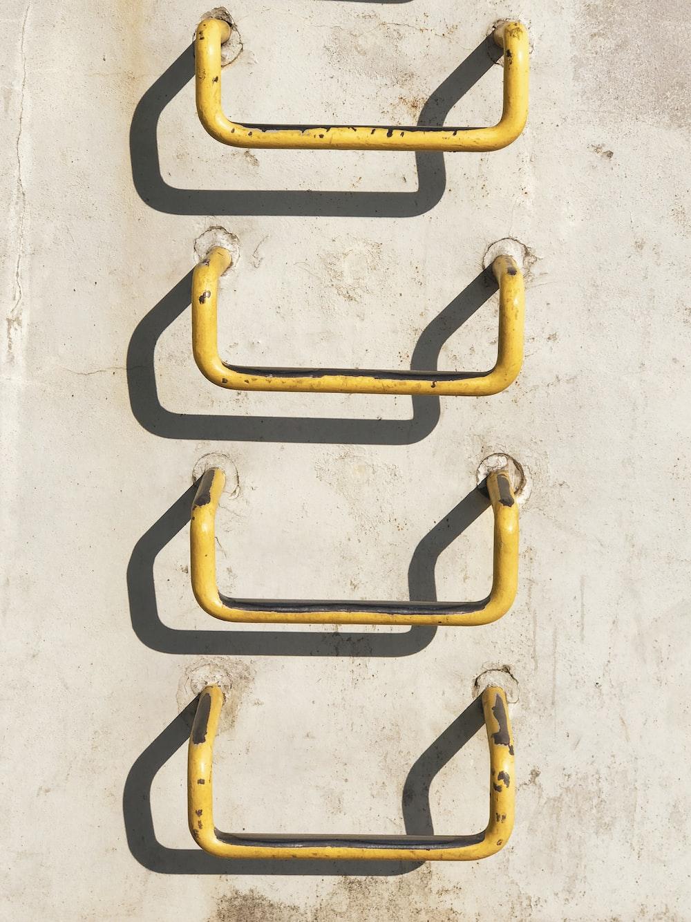 four yellow metal grab bars