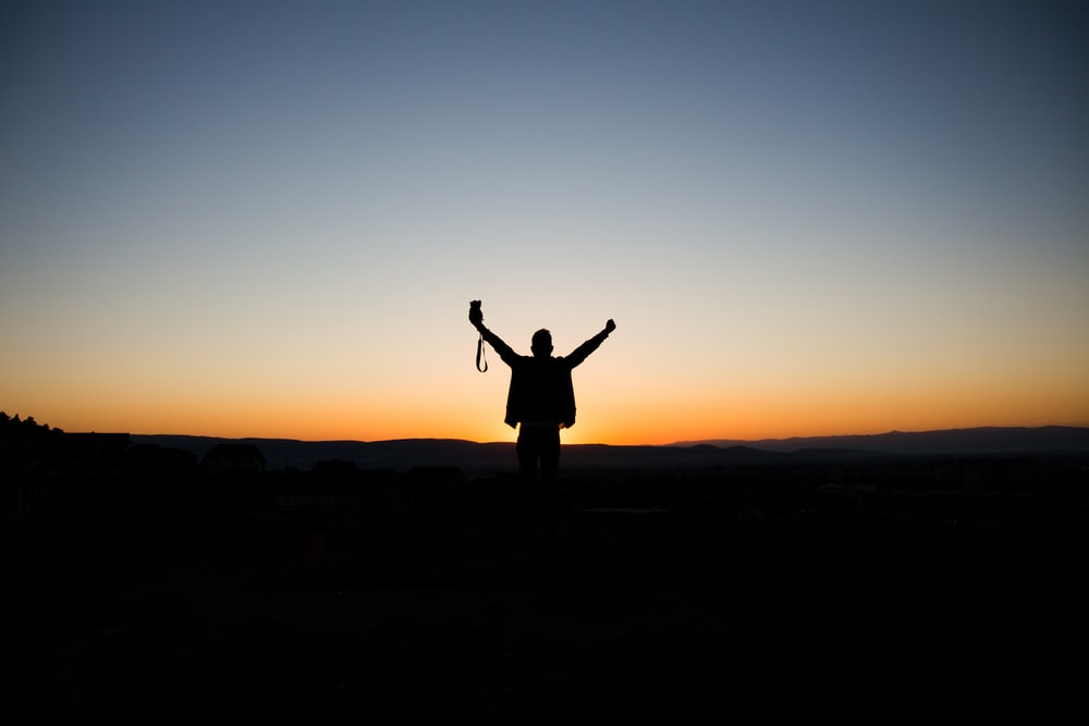 man stretching his arms silhouette at sunrise