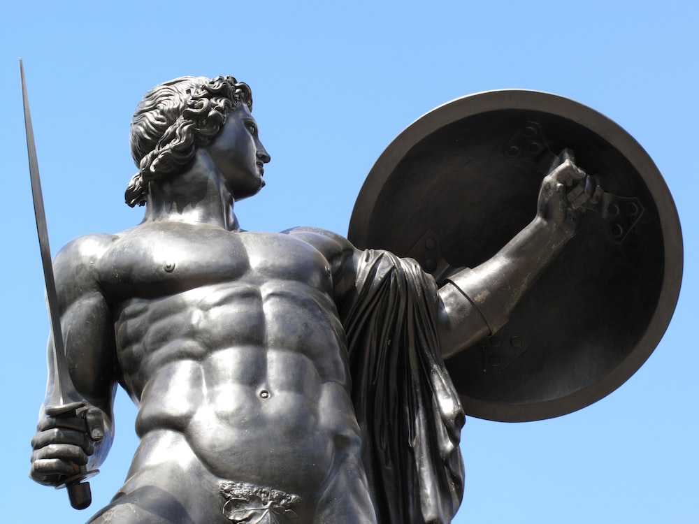 man holding sword and shield statue