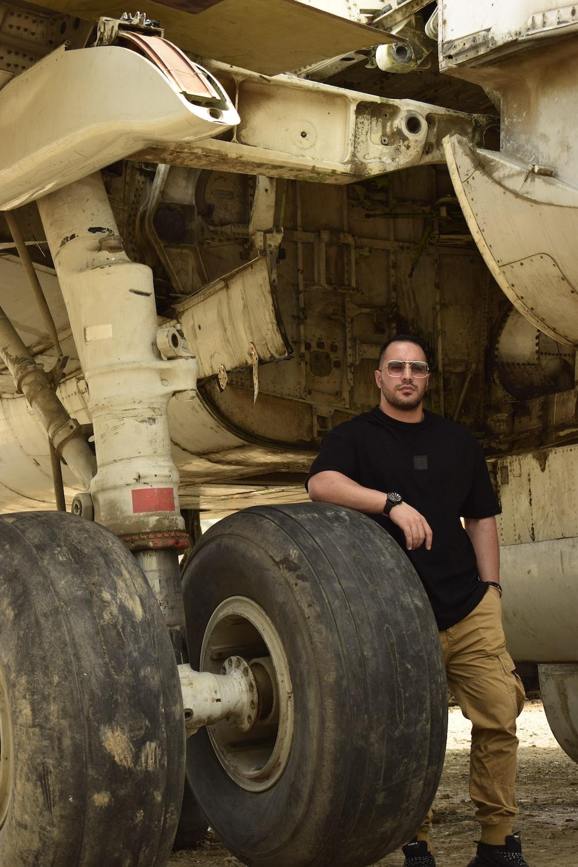 man in black crew-neck t-shirt standing near airplane wheel