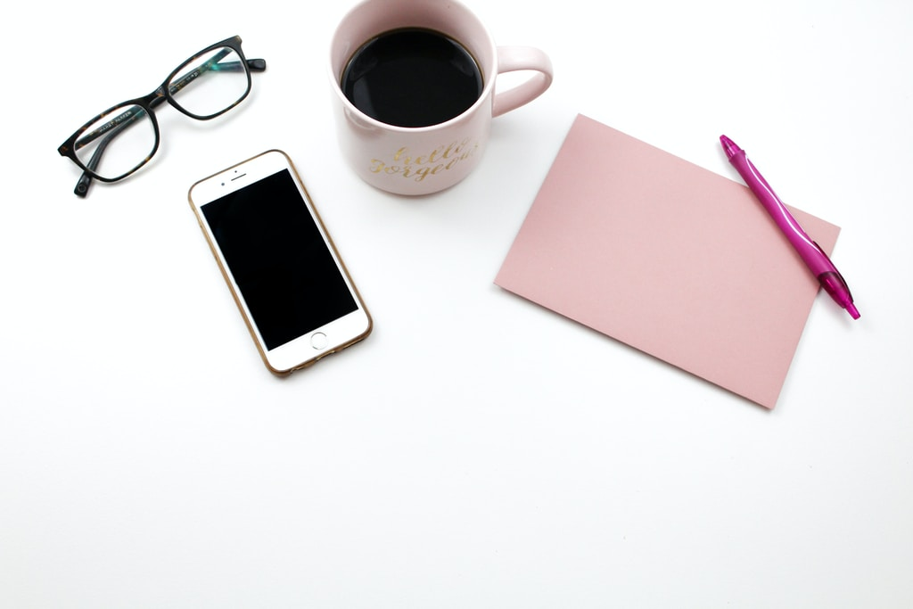 iPhone beside mugs with coffee, eyeglasses, and notes