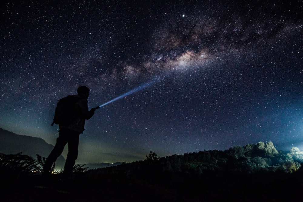 person carrying backpack standing near mountain during nighttime