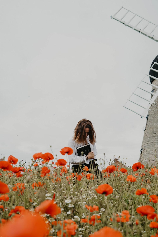 woman wearing white shirt holding black book near windmill