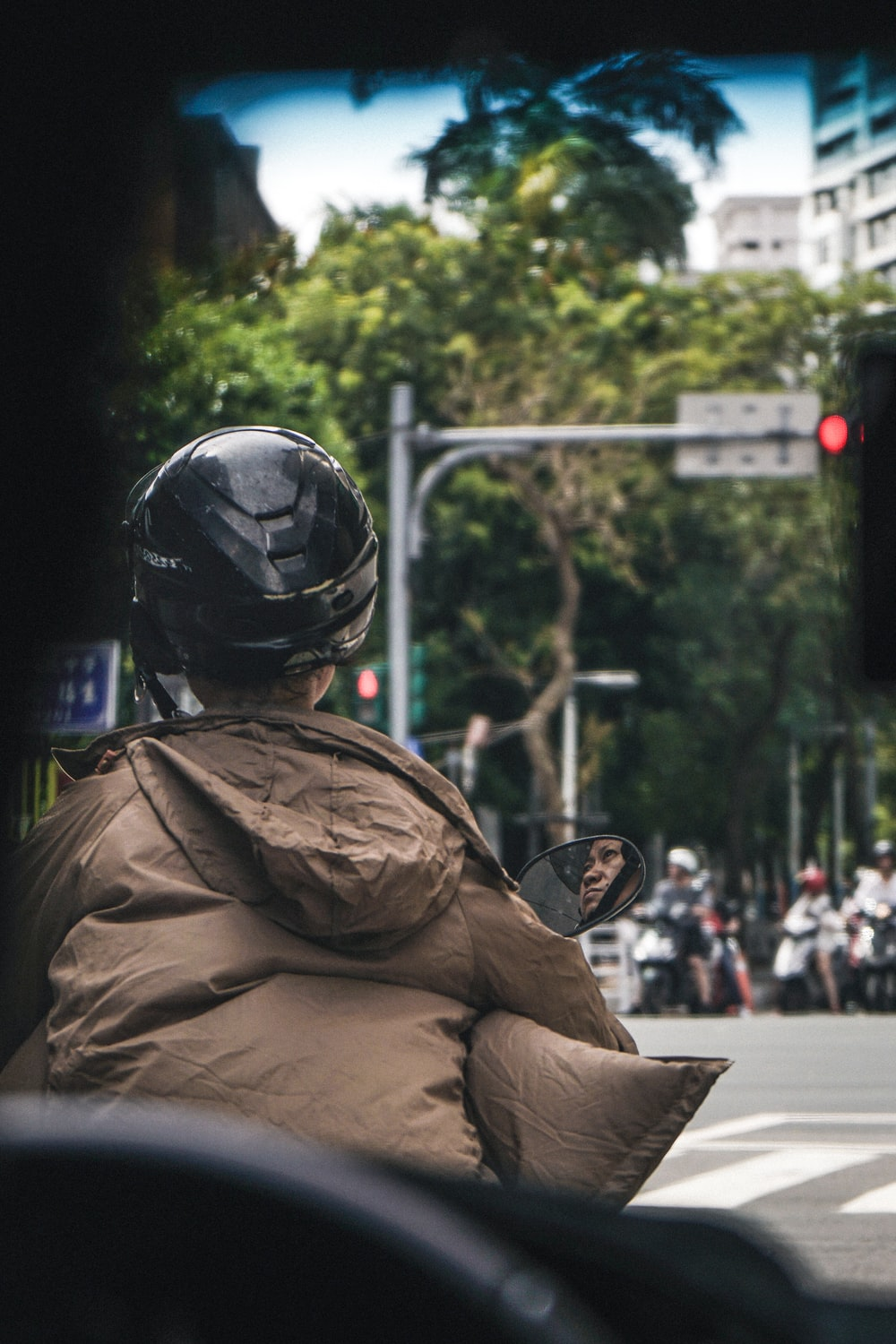 selective focus photography of person riding motorcycle near road during daytime