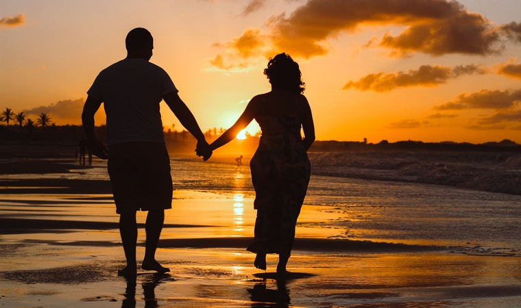 couple standing on body of water during golden hour