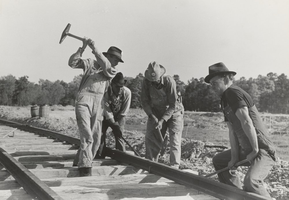 grayscale photography of four men holding mallet on train railway