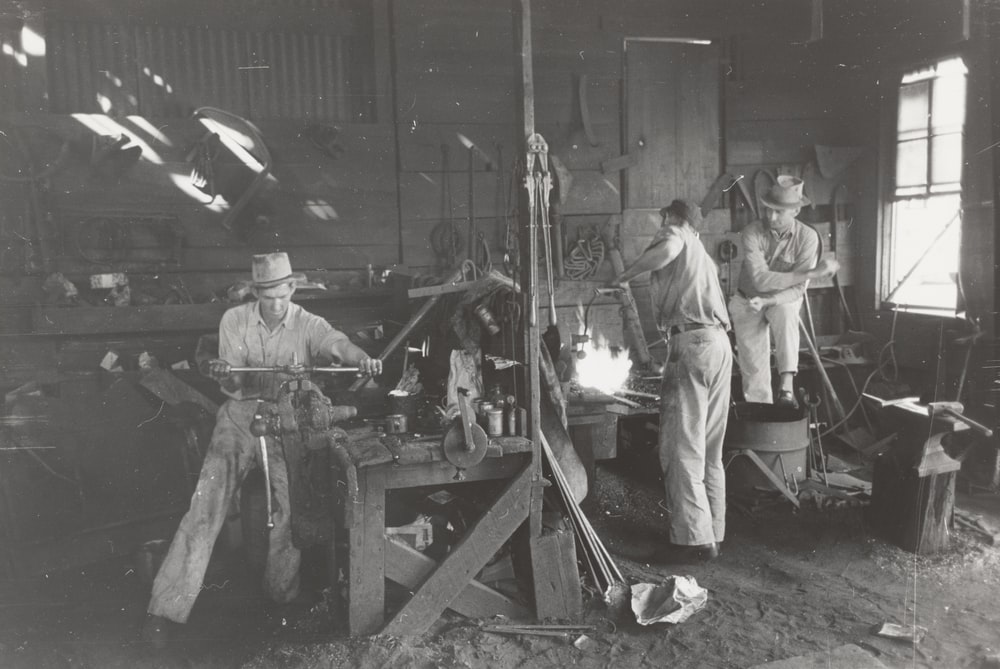 grayscale photography of men working inside building
