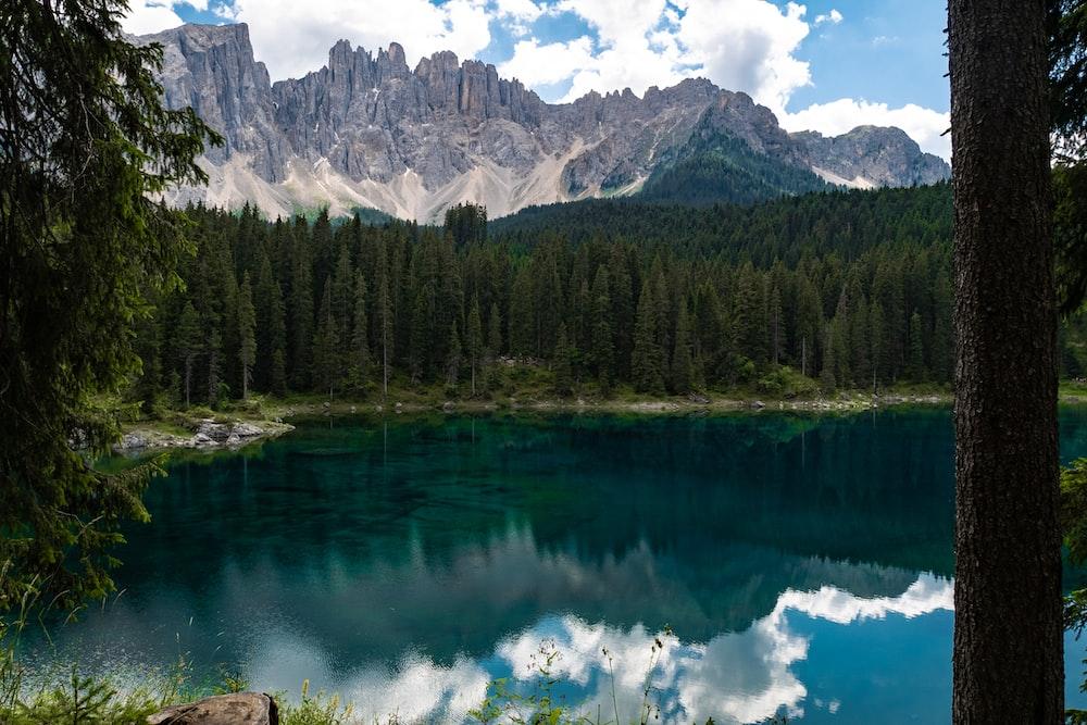 photography of lake and brown mountain range during daytime