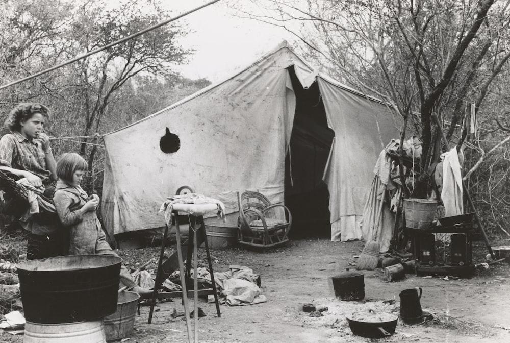 two women standing near tent