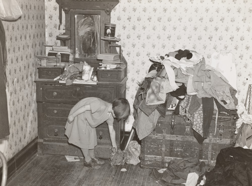 girl beside vanity dresser and clothes