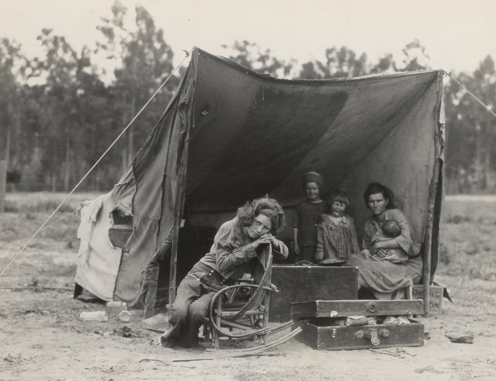 grayscale photography of two women with three children under tent