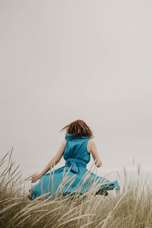 woman wearing blue dress standing on grass field