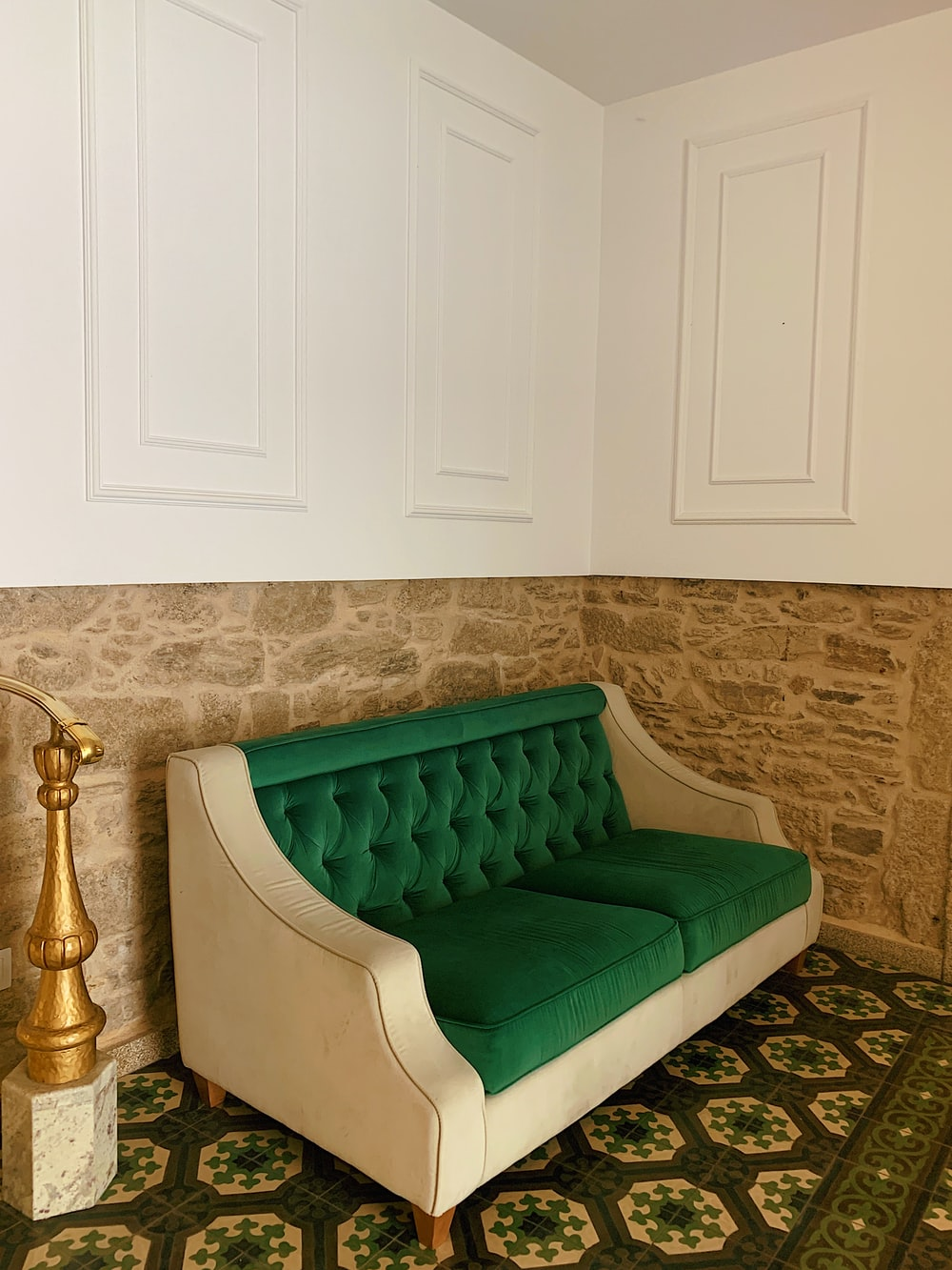 green tufted loveseat by the wall