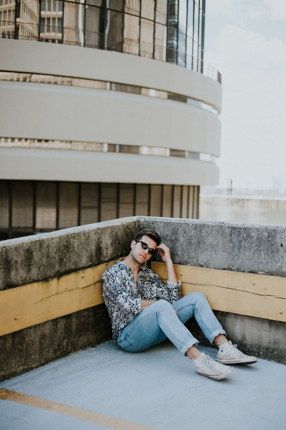 man in black and grey dress shirt and blue denim jeans sitting in building roof top floor