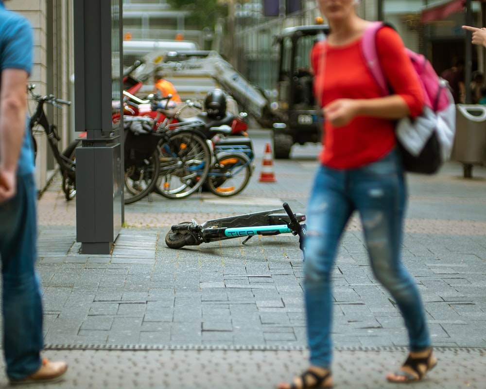 woman walking on pathway beside scooter on road