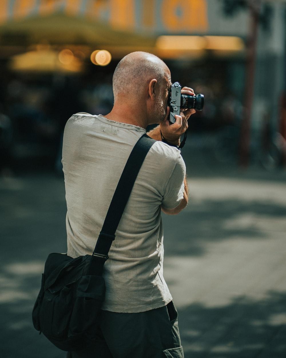 man wearing gray crew-neck T-shirt holding DSLR camera