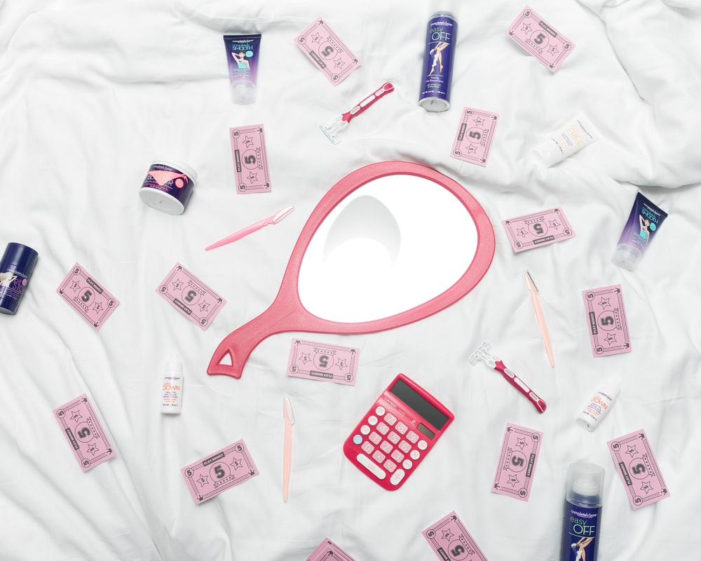 calculator, hand mirror, and toiletries in white textile