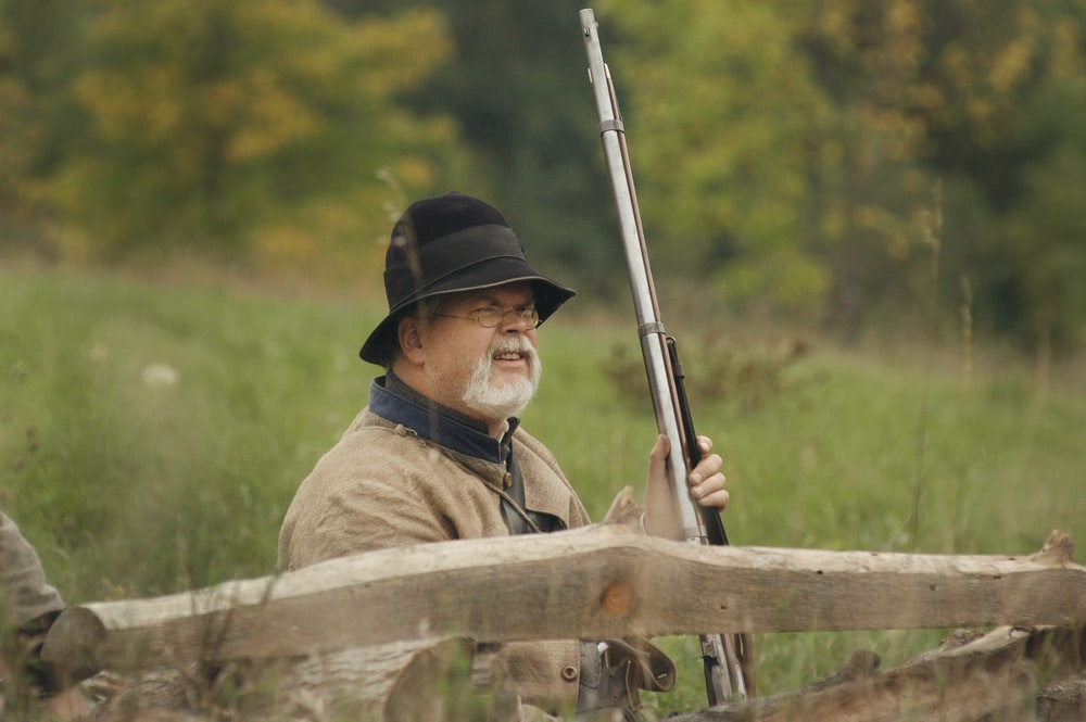man holding hunting rifle beside wooden fence