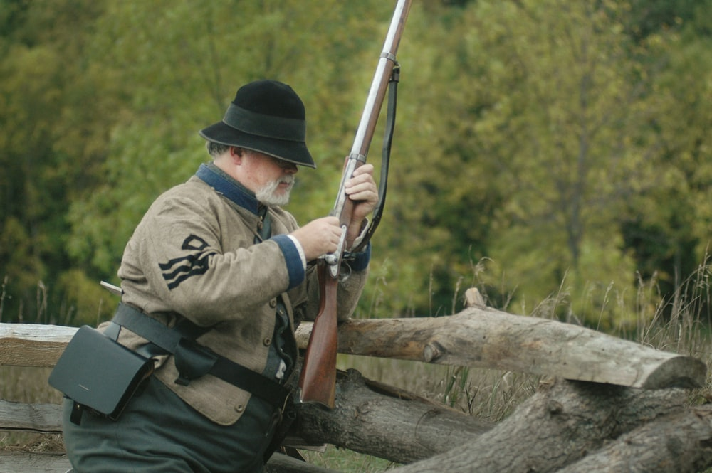 man using brown rifle