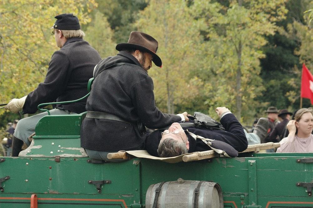 men lying on green vehicle