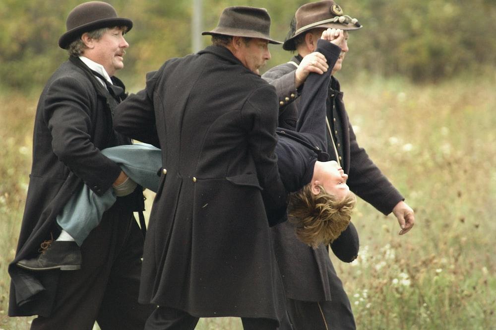 three men carrying man wearing black top