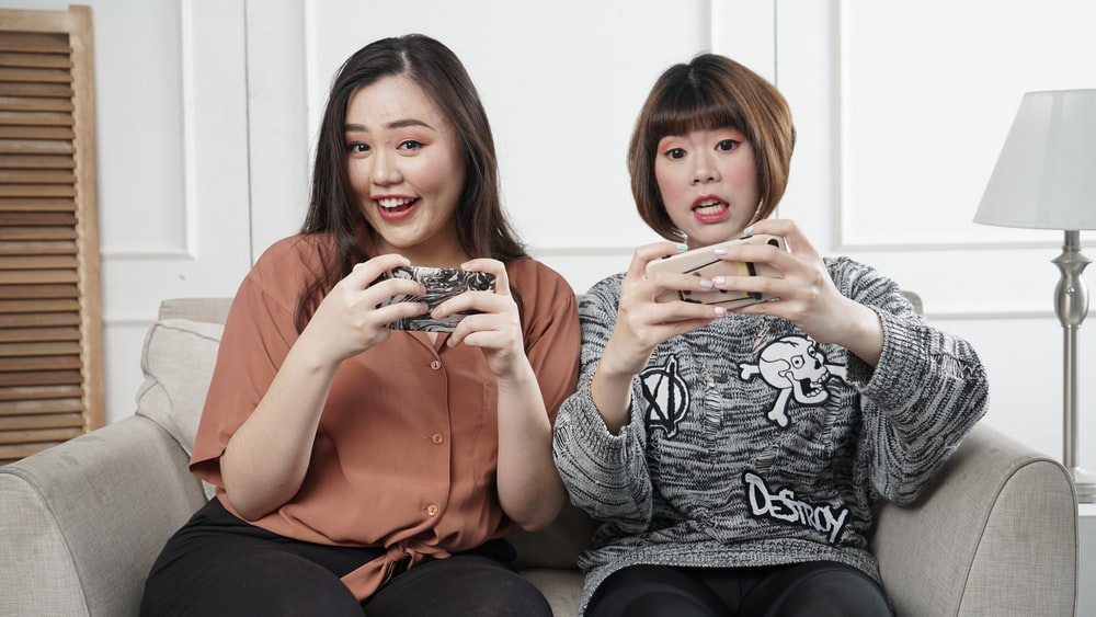 two women holding controllers sitting on sofa chair