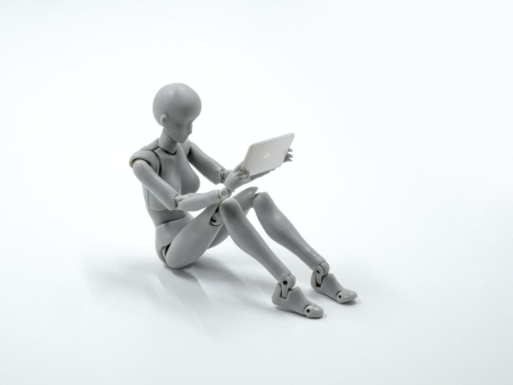 manikin figurine holding an iPad miniature