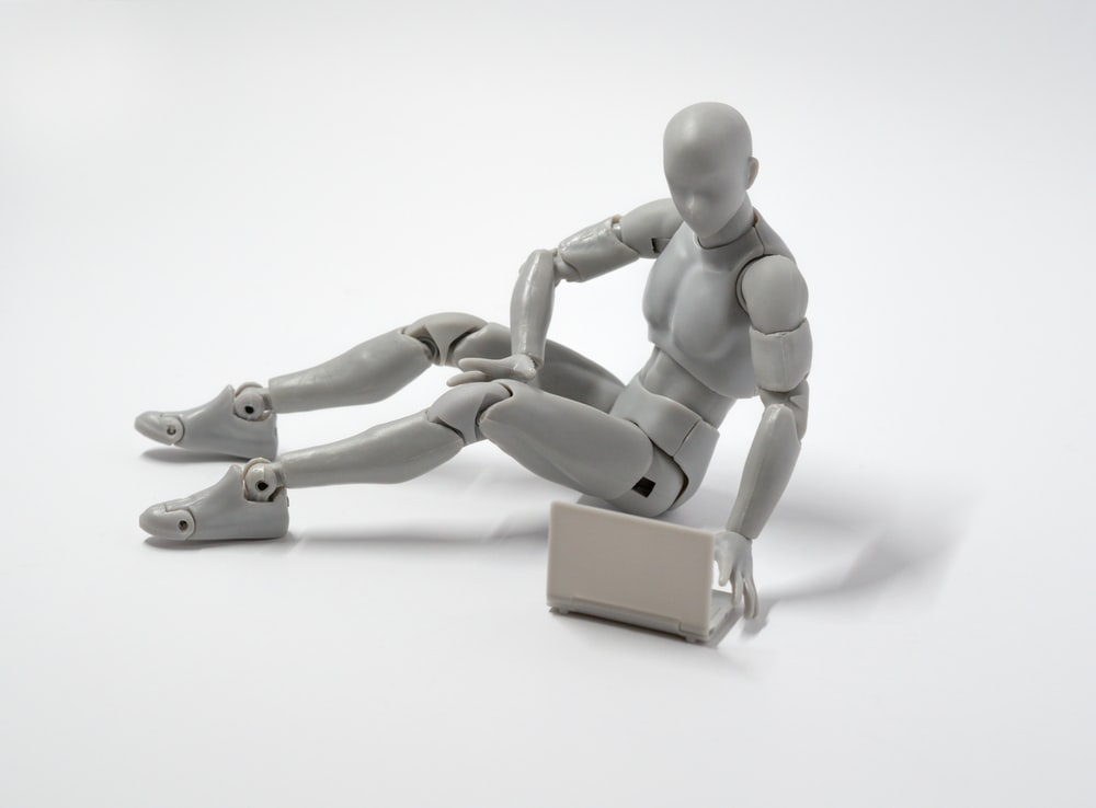 grey man action figure sitting on floor with laptop