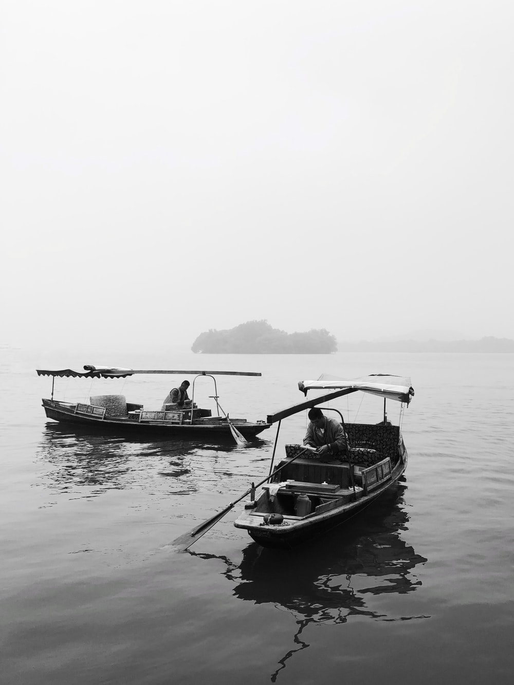 grayscale photography of two boats near island