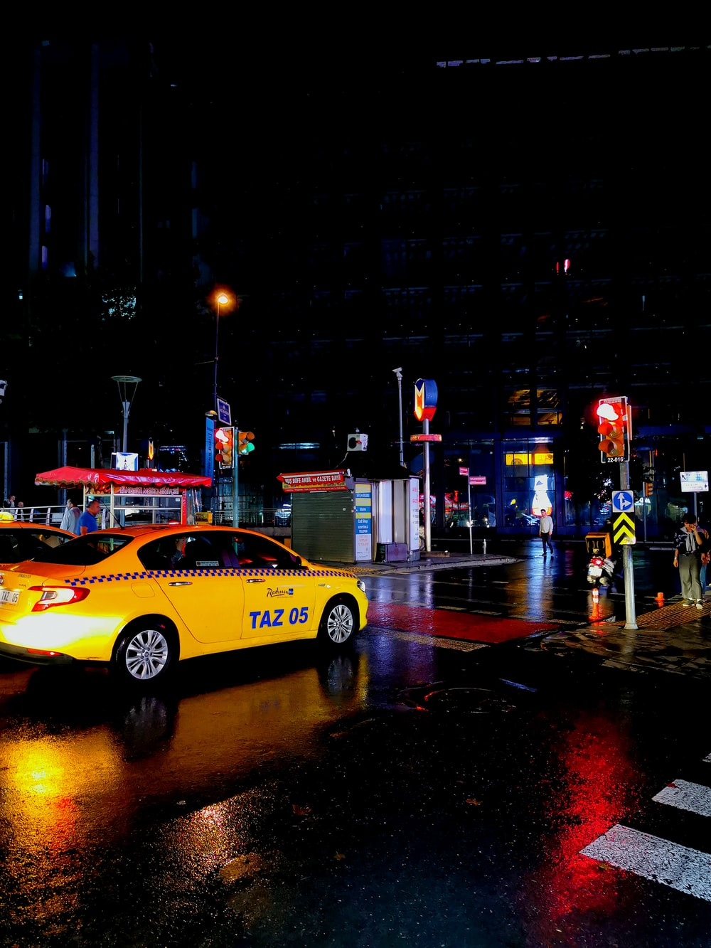 yellow taxi passing by wet road during nighttime