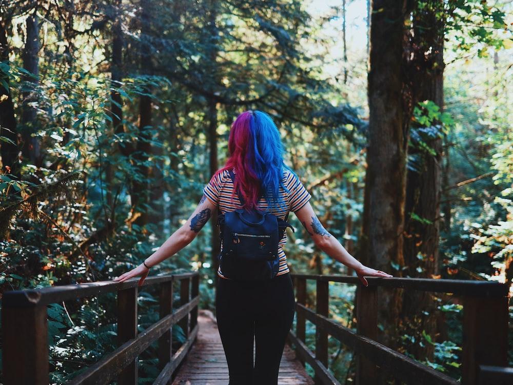 woman standing on brown wooden bridge