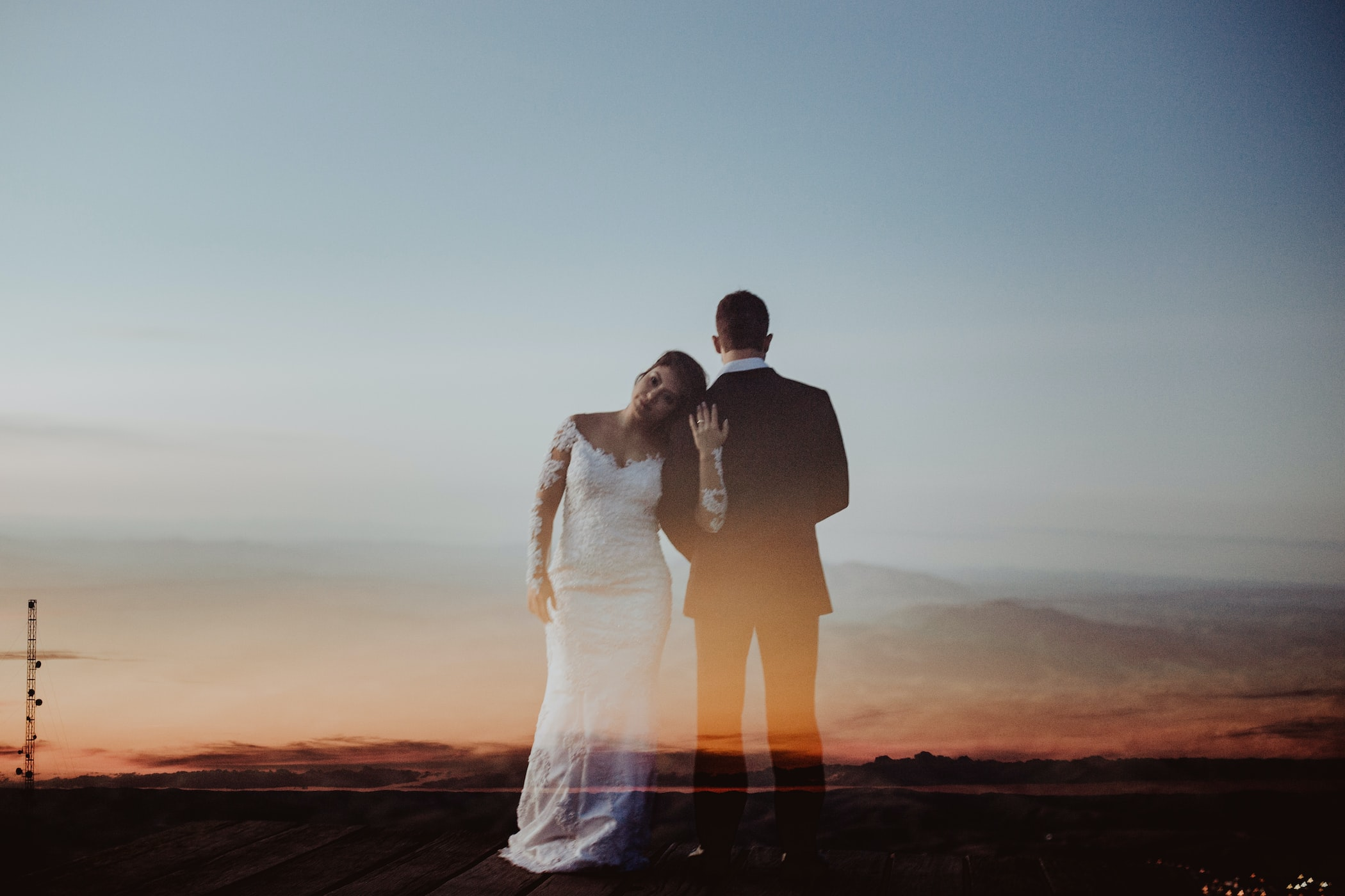 woman in wedding dress leaning her head to man's shoulder superimposed on a sunset