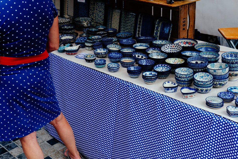 woman standing beside dinnerware set