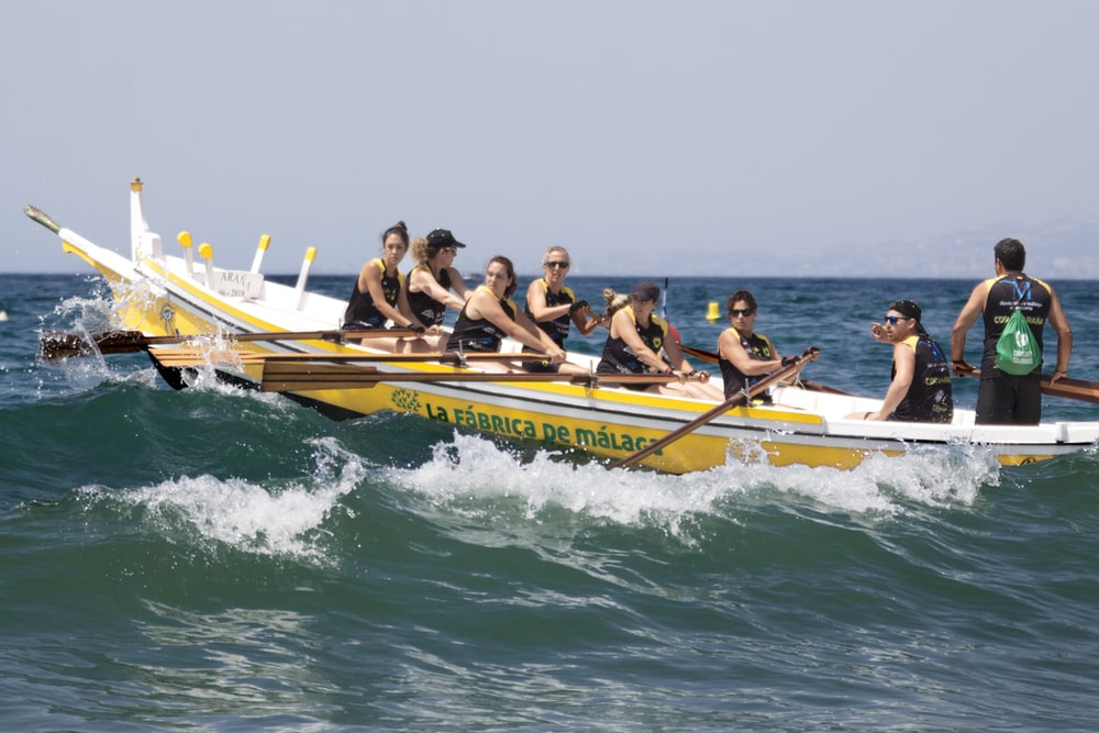 men riding on boat while rowing during daytime