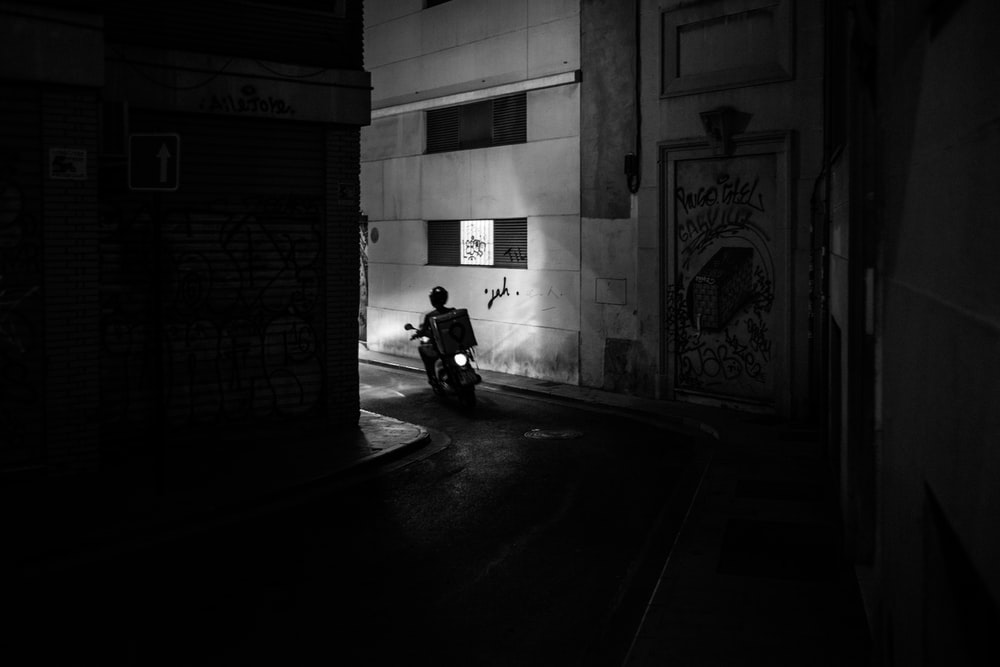 grayscale photo of a delivery motorcycle in an alley