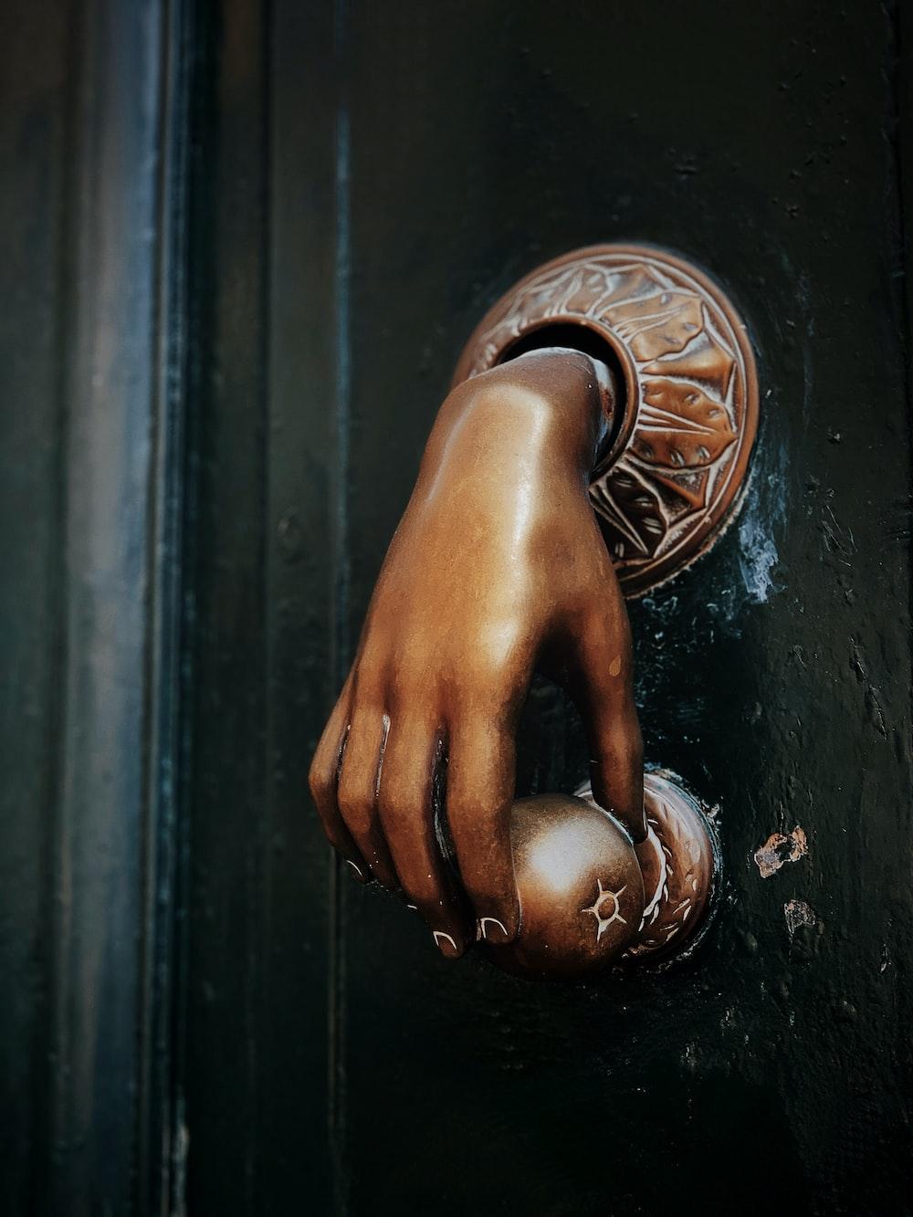 gold hand door knob