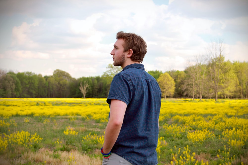 man in blue polo shirt and grey pants standing in yellow flower field