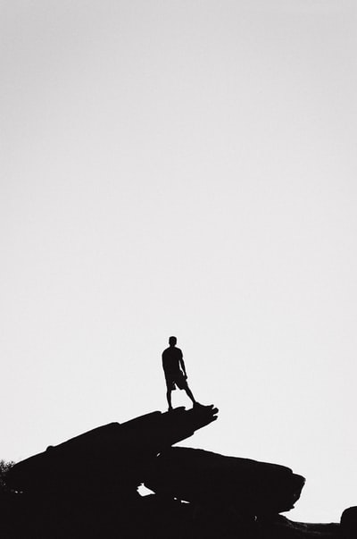 person standing in a rock formation grey-scale photography