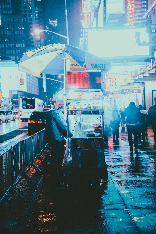 man with food stall in sidewalk