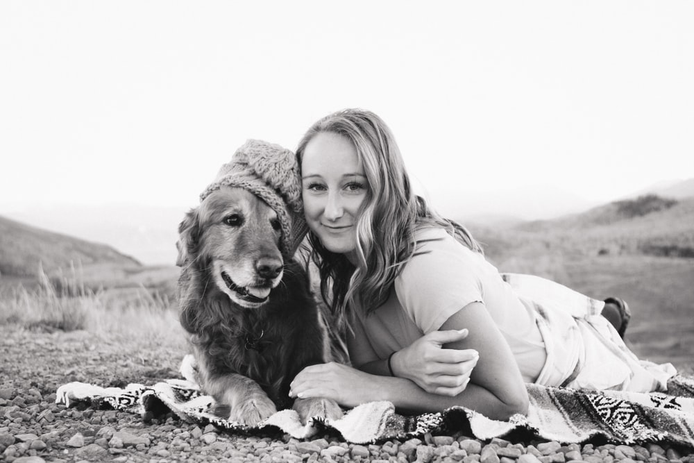 grayscale photography of smiling girl lying on textile beside golden retriever