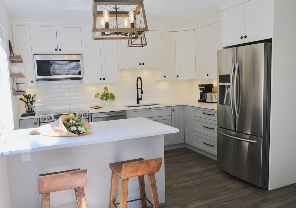 gray stainless steel 3-door French refrigerator and white kitchen island